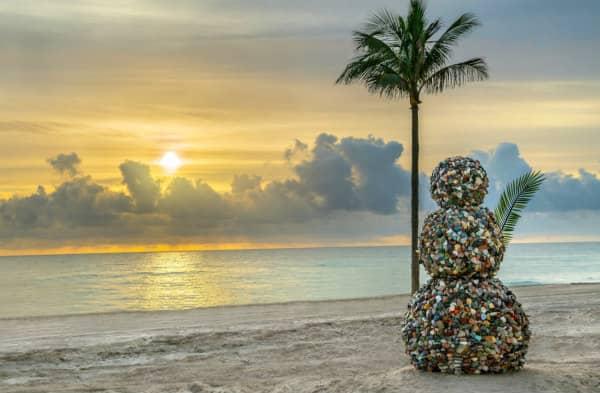 gemstone snowman sculpture on tropical beach at sunset