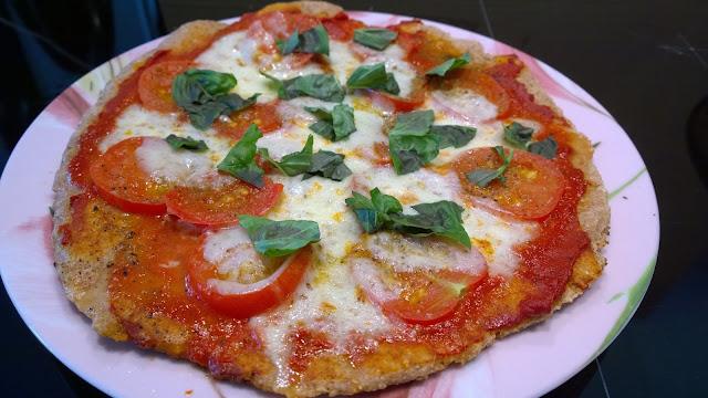 Pizza mit frischem Basilikum belegen  und genießen (c) by Joachim Wenk
