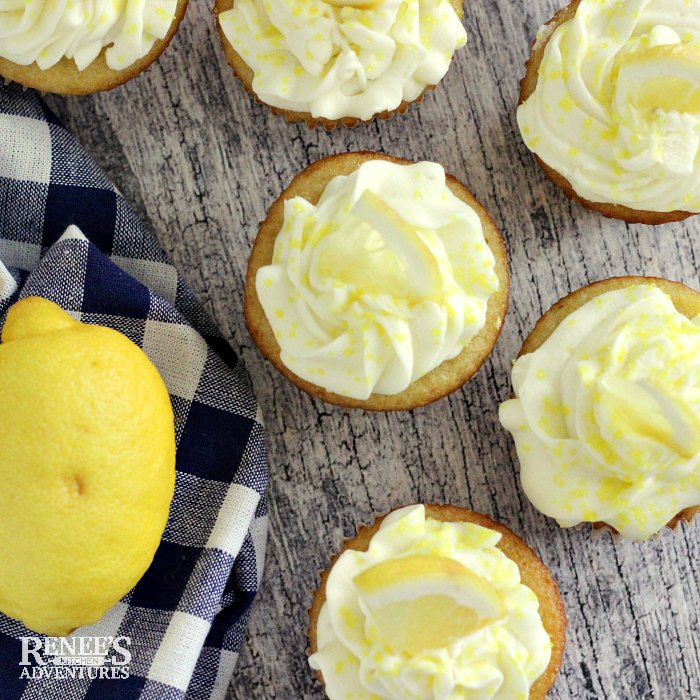 Easy Lemon Cupcakes by Renee's Kitchen Adventures overhead shot with cupcakes scattered on a board with a blue and white checked towel with lemons on it to the left