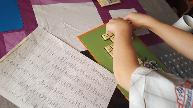 Working out his scrabble board for kids craft project