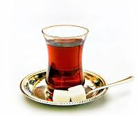 Yanında iki şekeri ve kaşığı dışarıda olan bir bardak çay