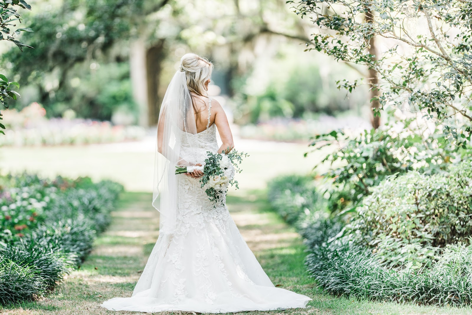 Image of bride in her wedding dress on the bridal walk in Airlie Gardens - wedding bouquet - garden wedding photography - Wilmington NC wedding photographers