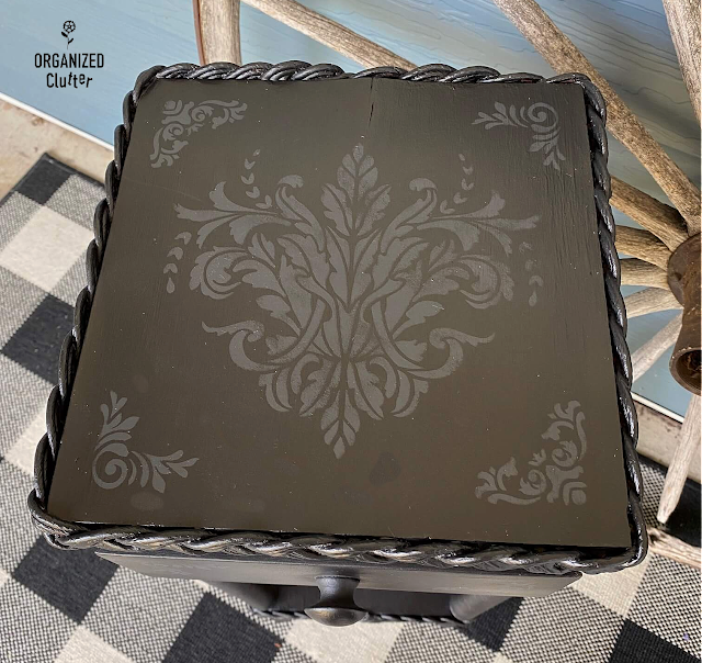 Photo of monochromatic stenciling on a black plant stand/table
