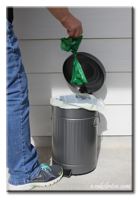 Tossing a dog waste bag in garbage can.