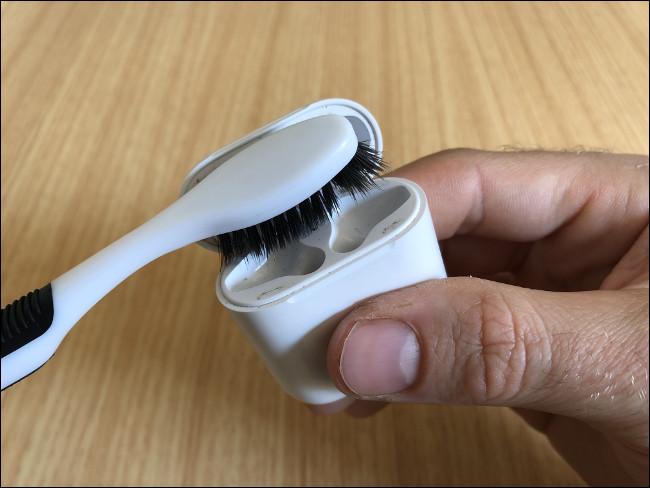 يد رجل تمسك علبة شحن AirPods وتنظيفها بفرشاة أسنان.