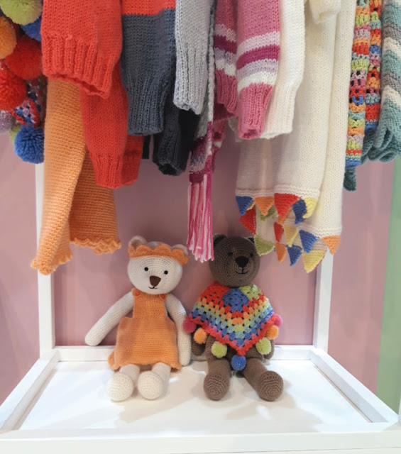 Image shows a white teddy bear in a mustard dress and crown sitting next to a brown teddy bear wearing a multi-coloured poncho.  They are hiding underneath some knitted garments