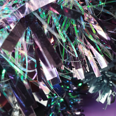 Iridiscent green and purple tinsel with almost transparent fronds, against the background of a dark purple wall. The image is very busy, and the tinsel takes up most of the image
