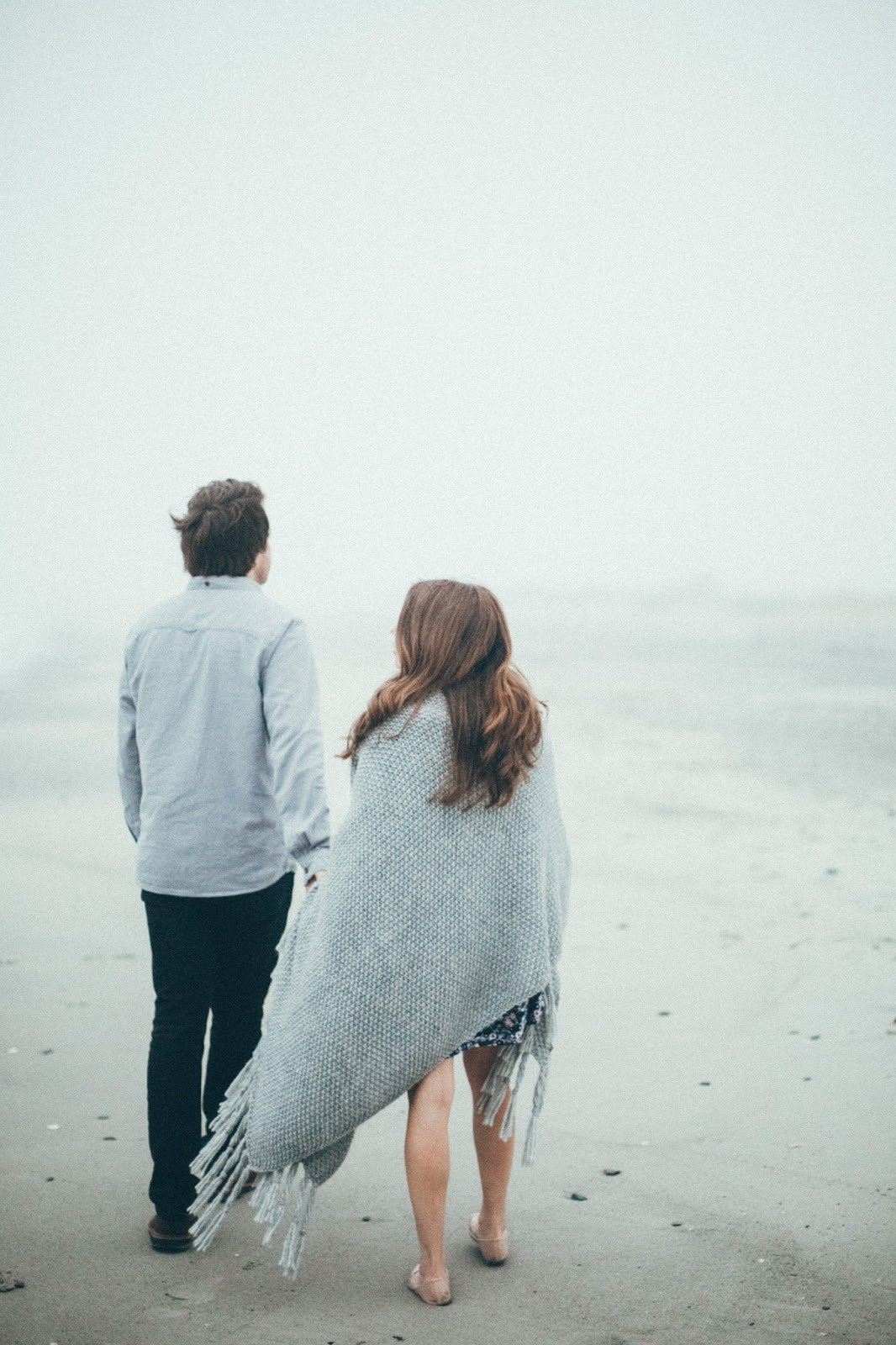 Man in grey jumper and woman wrapped in grey blanket on a beach