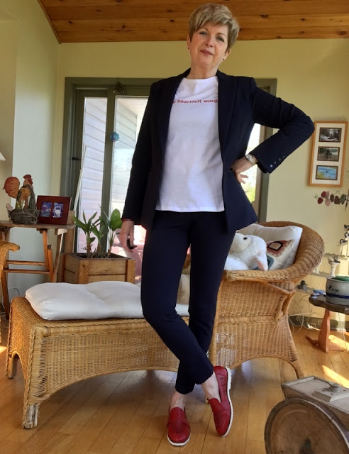 woman in navy suit, white tee, and red shoes