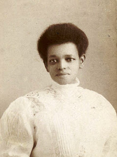 Portrait of a young African American woman in a white dress.