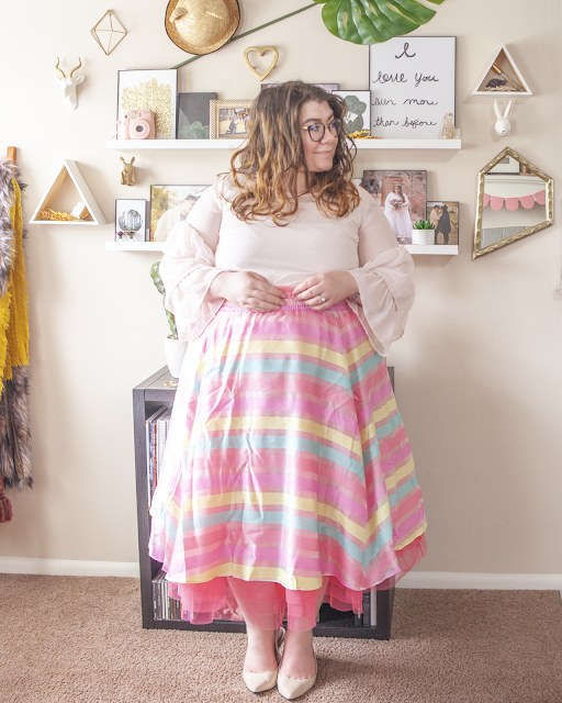 An outfit consisting of a light pink three tier ruffle sleeve blouse tucked into a pink, yellow and blue striped organza skirt with hot pink tulle and beige slingback heels.