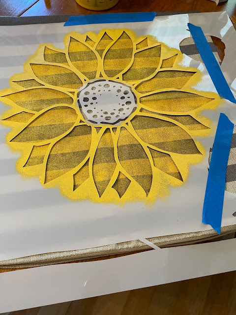 Photo of a sunflower being stenciled on a pillow cover.
