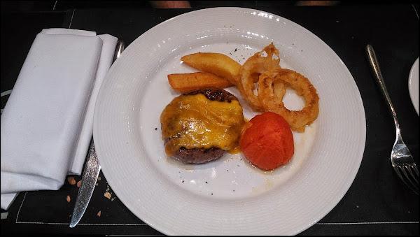Hamburguesa de buey con queso, aros de cebolla y tomate al horno Restaurante East 47 Madrid