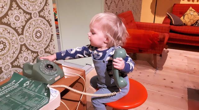 Lasten kaupunki, Helsingin kaupunginmuseo, museo, helsinki, lasten kanssa museoon, tekemista lasten kanssa helsinki, mummola, retromummola, retrotapetti, vanha puhelin, Foripaita, Kui design, oranssi jakkara