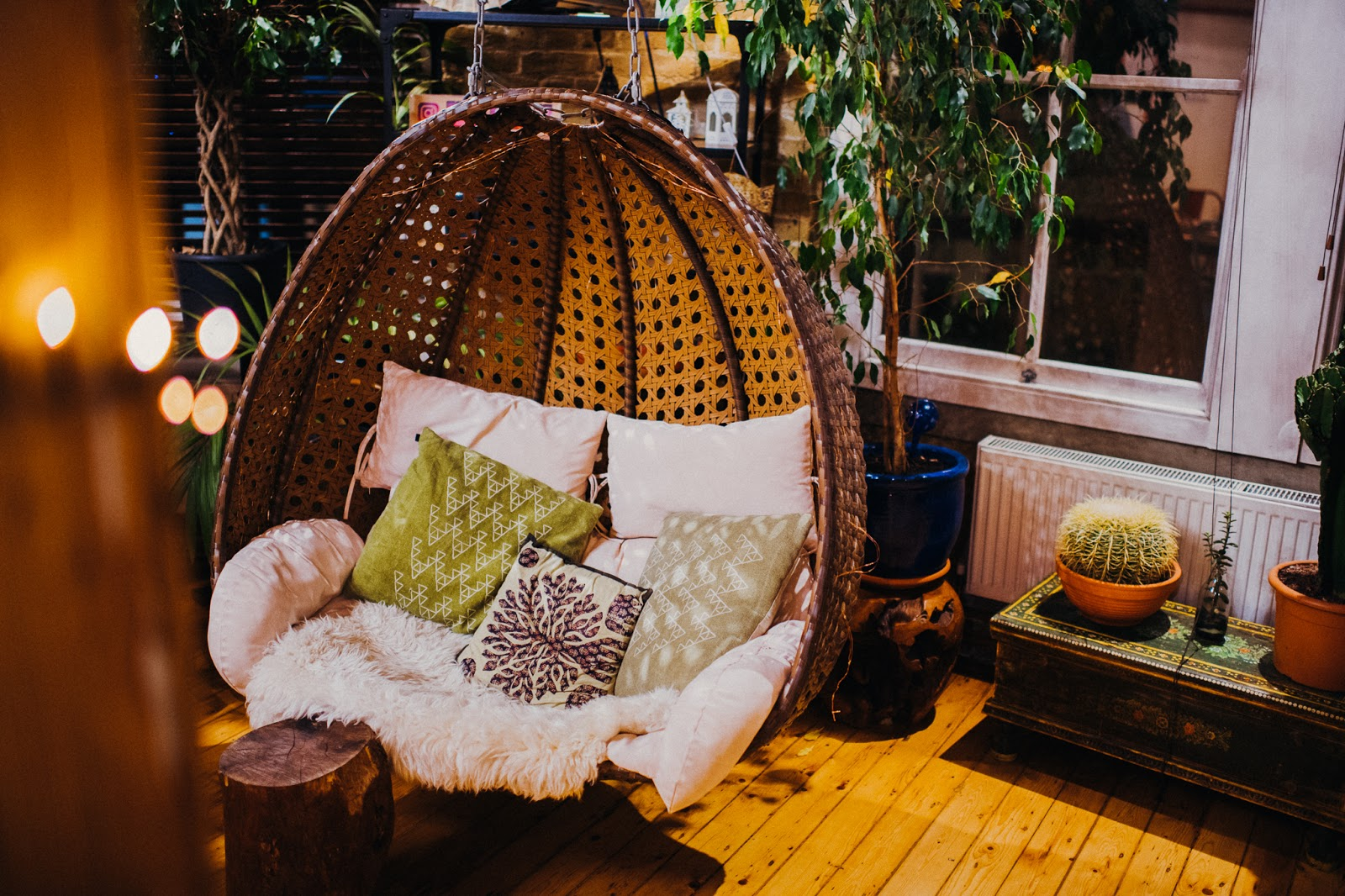 A hanging wicker chair with green and white cushions inside.