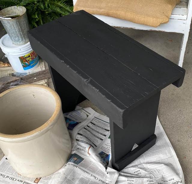Foto de um banco de madeira pintado de preto.