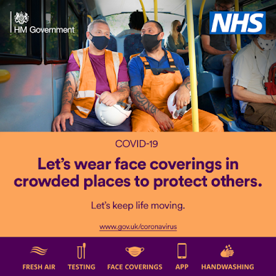 Wear face coverings in crowded places to protect others UK Gov 2 workmen sitting on a bus wearing masks and chatting together