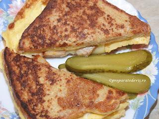 Reteta sandwich cald cu omleta impaturita retete culinare mancare din oua cu kaizer de porc castraveti si cascaval si felii de paine in ea pentru mic dejun sau gustare prajit la tigaie,