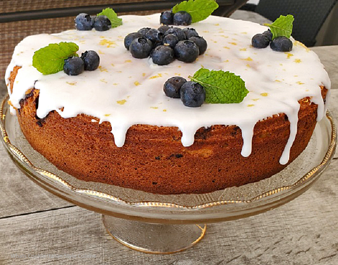 this is a blueberry doctored cake mix cake with a lemon frosting, lemon zest on top and blueberries, The cake is on a glass cake plate