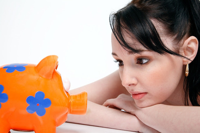 A woman staring at an orange and blue piggy bank