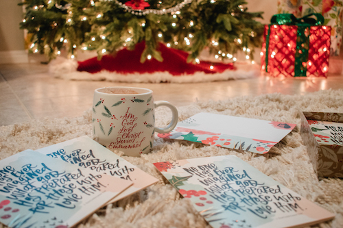 No One Has Ever Imagined Christmas cards on floor in front of Christmas tree with Names Of Jesus mug.