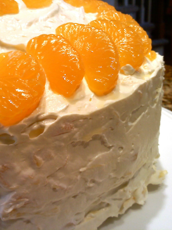 Mandarin Orange Cake | A moist and fluffy cake recipe made with a cake mix and mandarin oranges topped with the famous cool and creamy icing made with crushed pineapple, pudding mix and cool whip. Also known as Pig or Pea Pickin' Cake, Sunshine Cake and Ambrosia Cake.