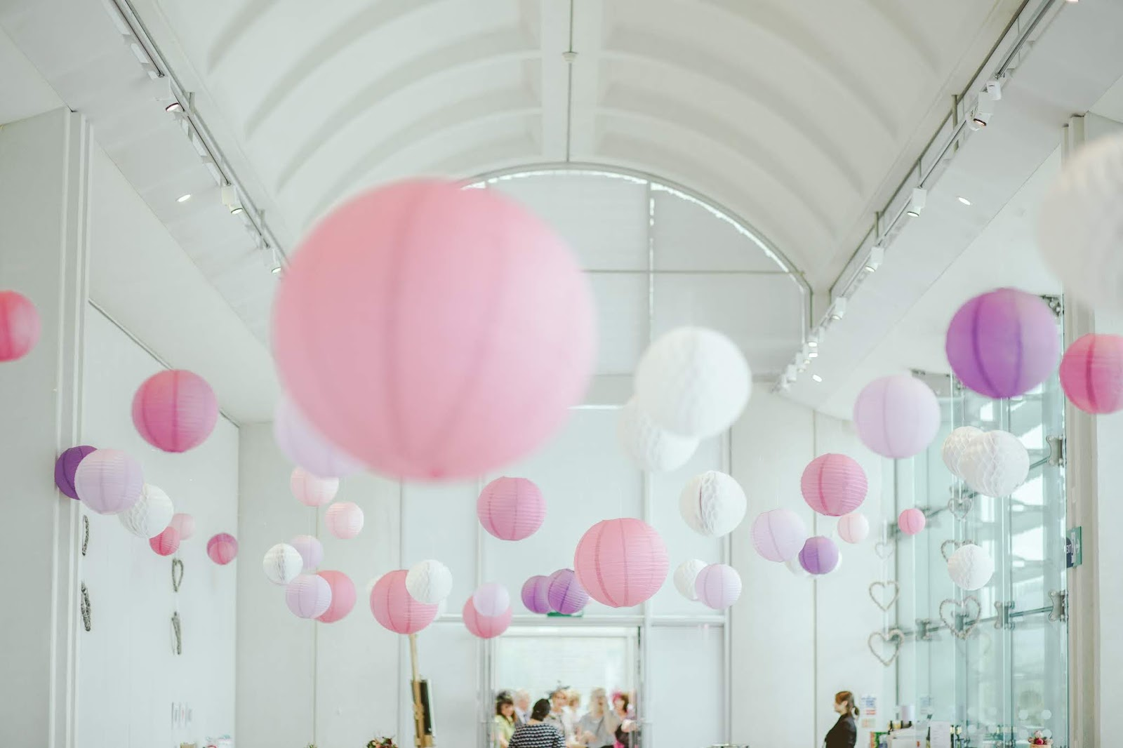 Photography of a party scene with hanging decorations of pink and purple paper lanterns.