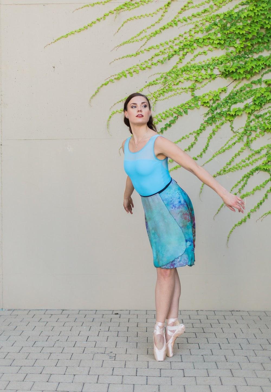 Author Joanna Marsh stirkes a pose en pointe outside.