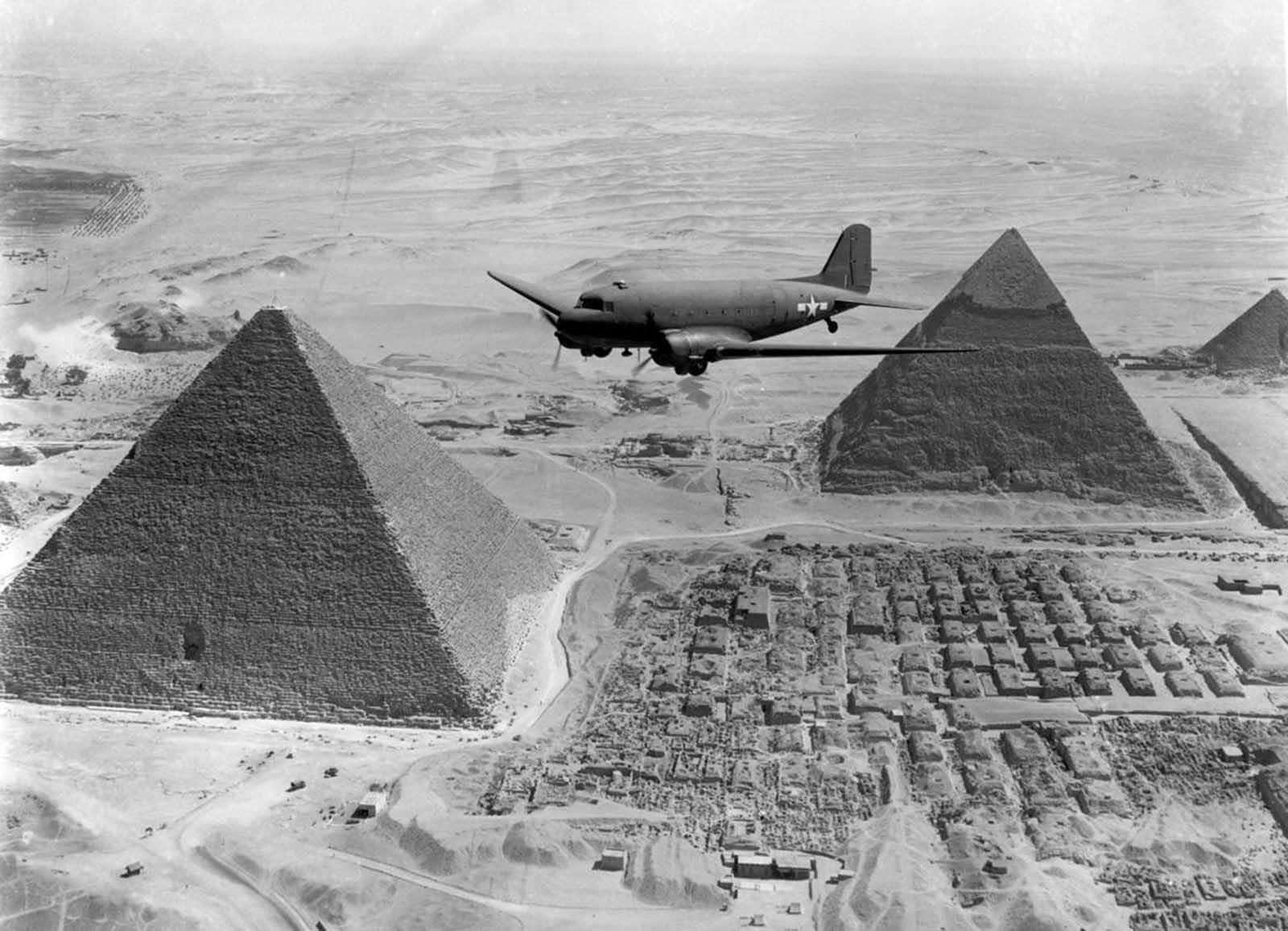 After the defeat of Axis forces in Northern Africa, Allied troops prepared to use the territory to launch attacks on Italy and other parts of southern Europe. Here, a U.S. Air Transport Command plane, loaded with war supplies, flies over the pyramids at Giza, near Cairo, Egypt, in 1943.
