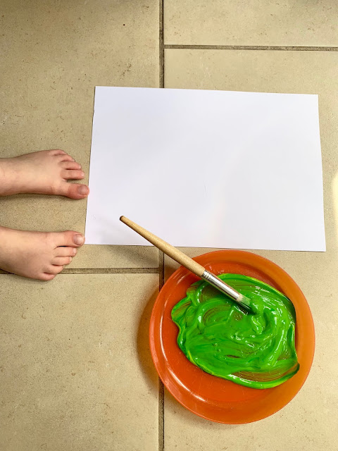 Toddler feet next to white card and a plate with green paint