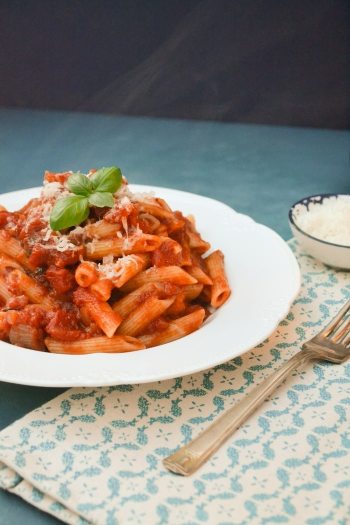 A bowl of pasta coasted in tomato and basil sauce
