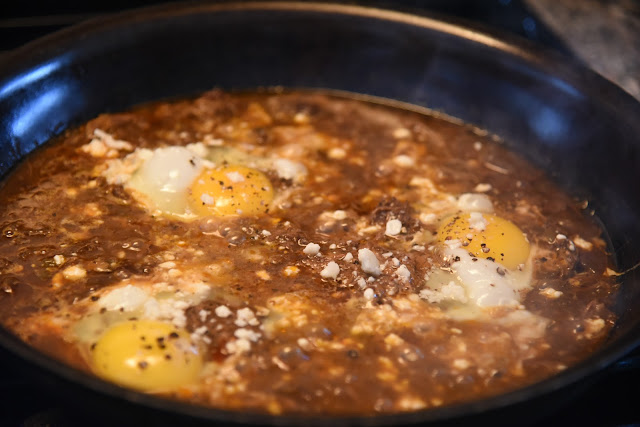 chipotle barbacoa reheated in a skillet, topped with eggs and cotija cheese