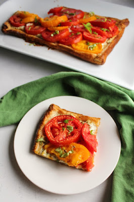 First slice of tomato tart served on plate with remaining tart in background