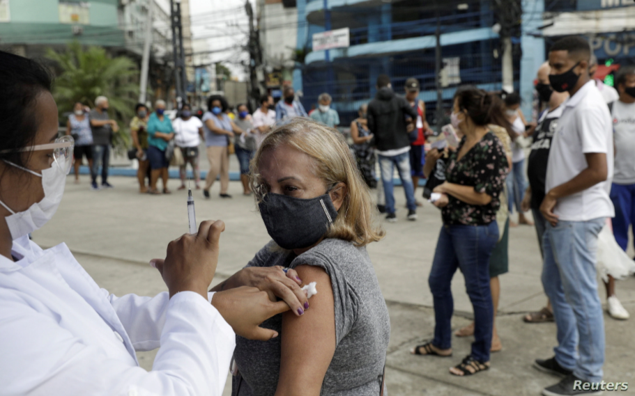 Un trabajador de la salud administra una vacuna a una mujer en Río de Janeiro, Brasil en abril de 2021 / REUTERS