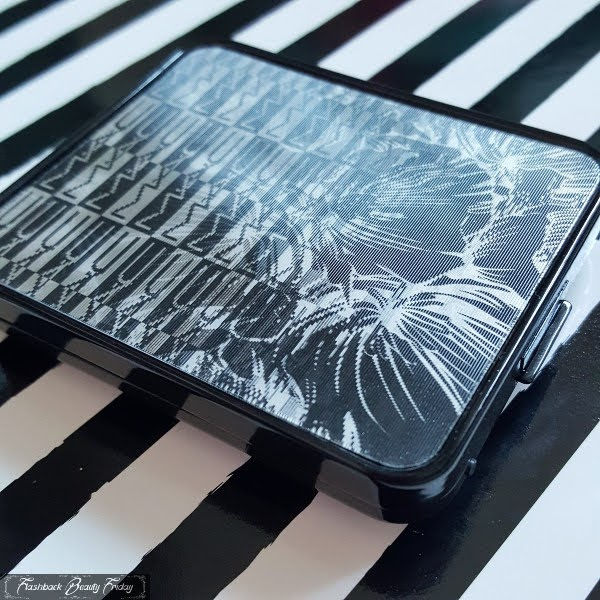 shiny black eyeshadow palette sitting on striped back with MAC logo and floral hologram lid