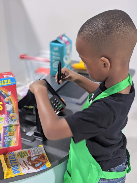 preschooler playing with register at supermarket at Little Play Place