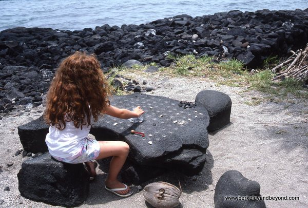 child playing konane checkers in Pu'uhonua O Honaunau National Historical Park/City of Refuge in Honaunau on Big Island, Hawaii