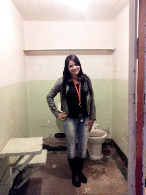 mulher em uma cela de prisao pequena e sem cama