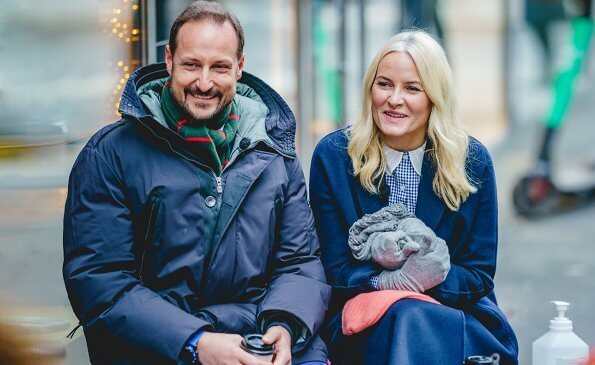 Crown Princess Mette-Marit wore a navy blue wool cashmere coat and camel leather boot. Peter Pan collar blue and white blouse with gingham check