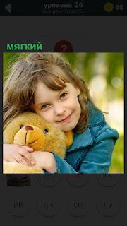 девочка на улице в руках обнимает мягкую игрушку медведя плюшевого