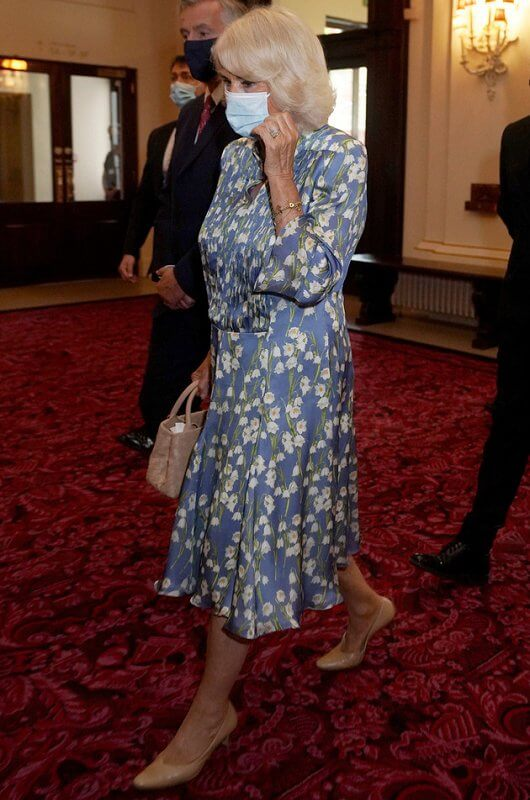 Camilla wore a floral silk blue dress from Fiona Clare, and she carried beige leather bag from Bottega Veneta