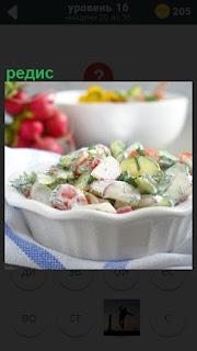 На столе стоит миска с приготовленным салатом из редиса