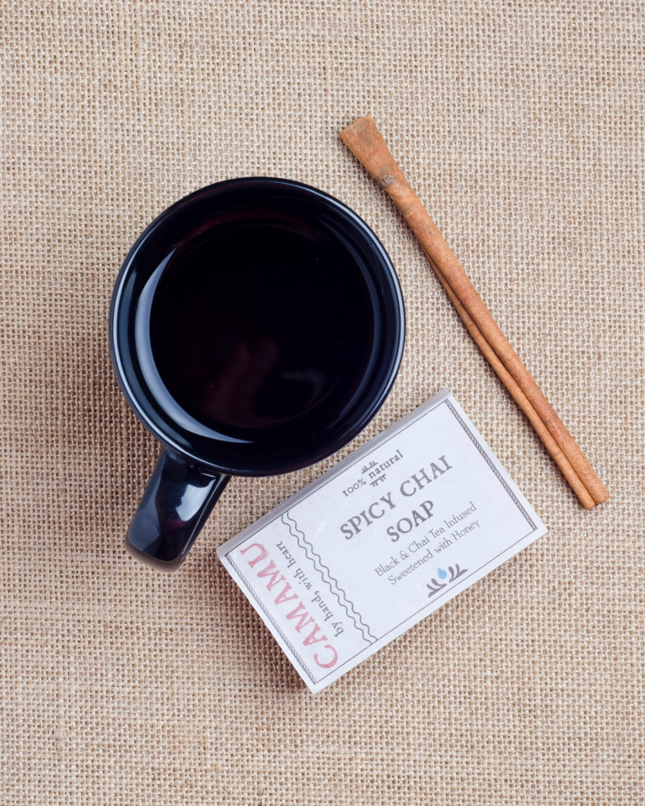Camamu Spicy Chai Soap flatlay with mug of tea and a cinnamon stick