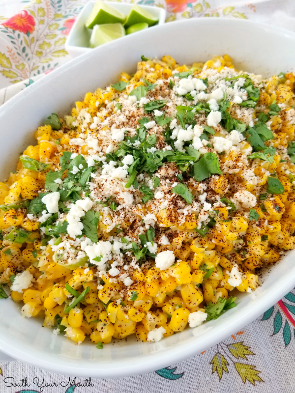 Mexican Street Corn (Esquites) served off the cob as a side dish or warm salad with Mexican crumbling cheese, a creamy spread, fresh cilantro and chili powder.