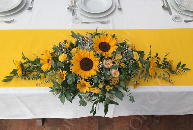 Esküvői asztaldísz napraforgóból és sárga virágokból, rózsából
