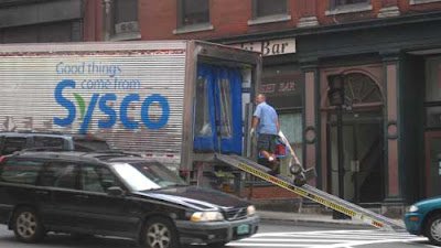 Silver Sysco truck unloading on the street with ramp down, blue and green logo with leaf and the tag line Good things come from Sysco