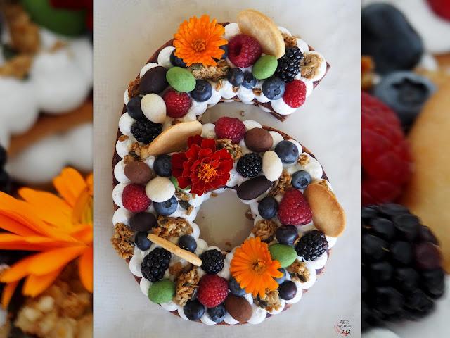 Tarta Adikosh o number cake con base de galleta de masa sucrée, relleno de orange curd y merengue italiano, y decorada con frutos rojos, granola, catanias y flores.