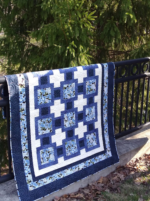 Blue and cream floral quilt draped over iron railing