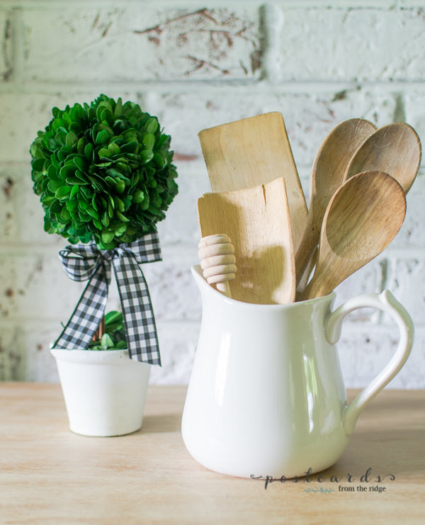 preserved boxwood topiary and vintage wooden spoons in white stoneware pitcher