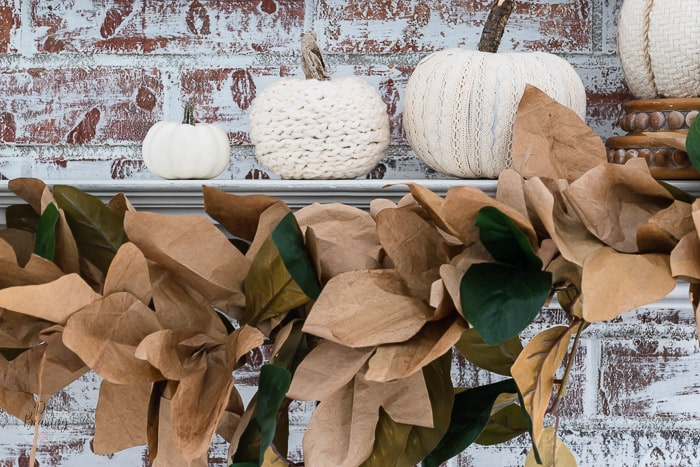 brick painted fireplace with fall leaf garland and neutral pumpkins